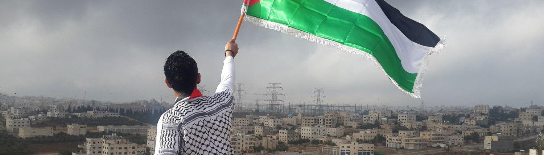 Vyras, laikantis Palestinos vėliavą. Tolumoje – miestas