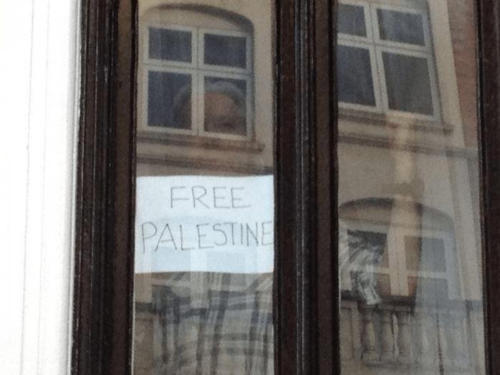 """Julianas Assange'as su plakatu """"Free Palestine"""" Ekvadoro ambasadoje per 2014 m. Izraelio karinę ataką prieš Gazą."""